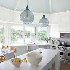 Bright, airy light blue kitchen with centre island and cliffside view