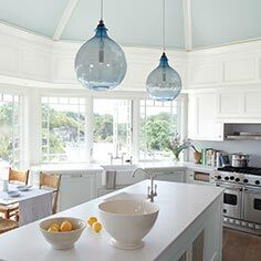 Bright, airy light blue kitchen with center island and cliffside view
