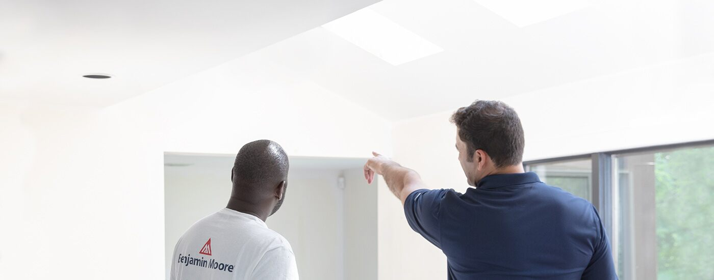A contractor and customer review a white room with big windows.