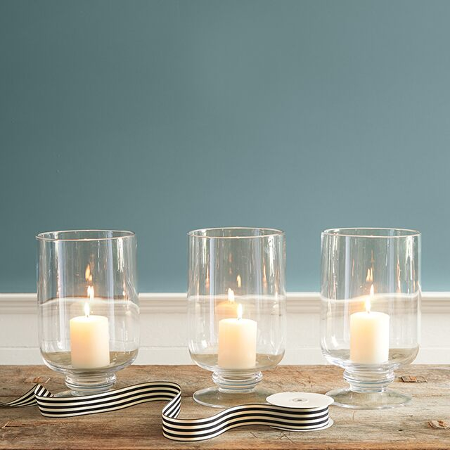 Close up of three candles placed in clear jars in front of Aegean Teal 2136-40 wall.
