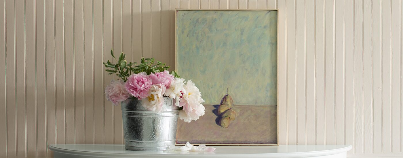 Pale pink walls with a painting and a tin bucket of pink flowers on top of a console.