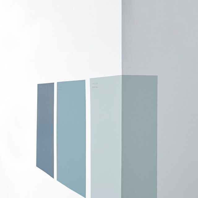 Three peel-and-stick samples in different blue paint colors being applied to a white-painted wall.