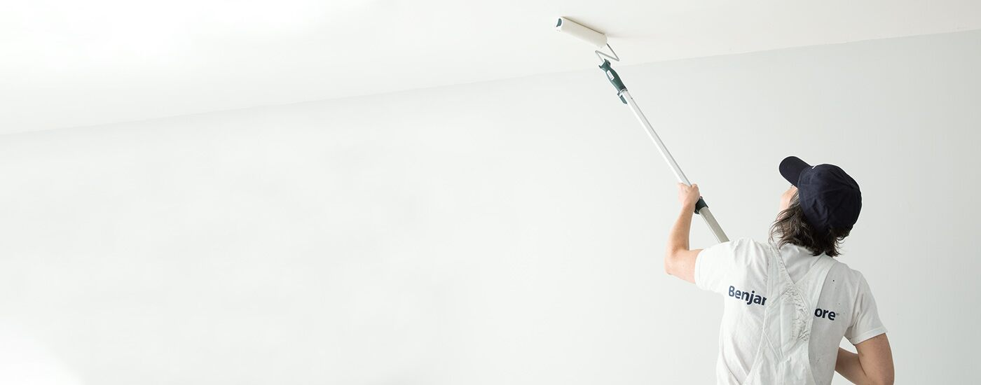 A Benjamin Moore painting contractor in overalls uses a roller to paint the ceiling of a white room.