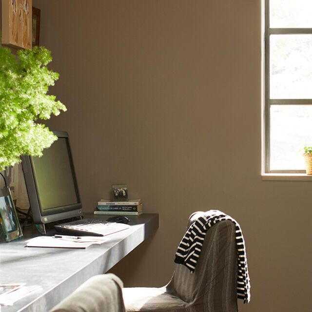 A home office featuring warm brown walls and a desk with plants, a computer and trinkets; a striped sweater is thrown over the chair.
