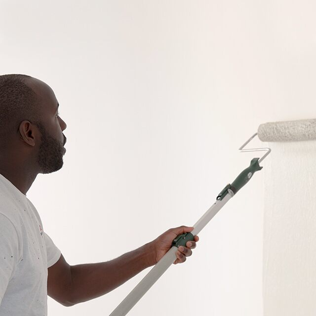 A painting contractor rolling white paint onto a primed wall.