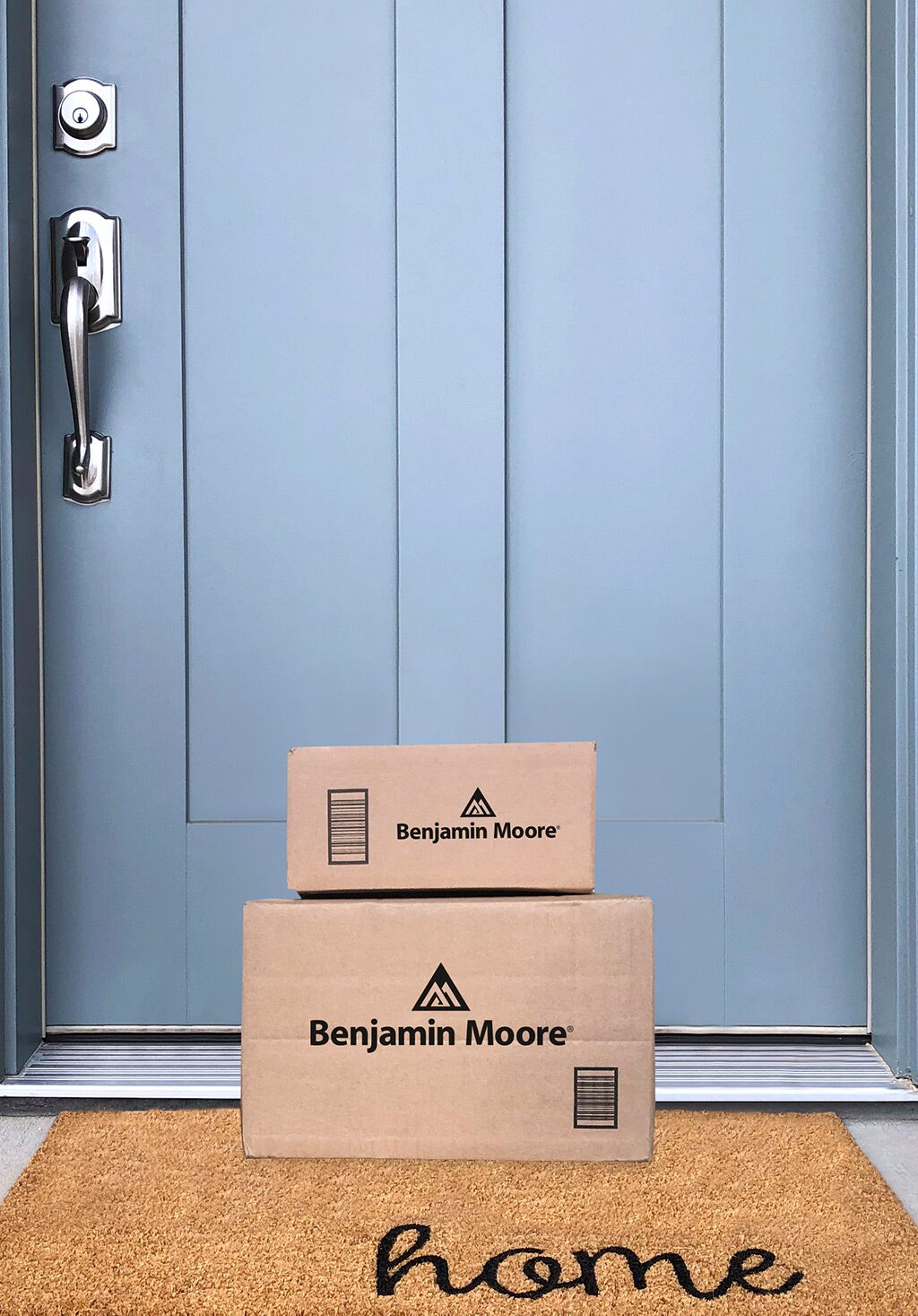 A package containing paint and supplies from Benjamin Moore sits in front of a door painted in Harlequin Blue 830.