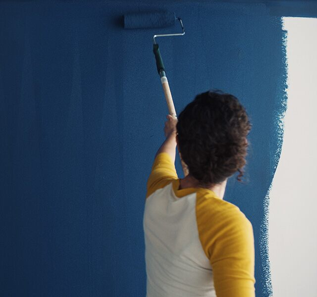 A homeowner uses a roller to paint Symphony Blue 2060-10 on a wall.