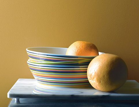 Dinner plates in variety of bright colors against yellow wall