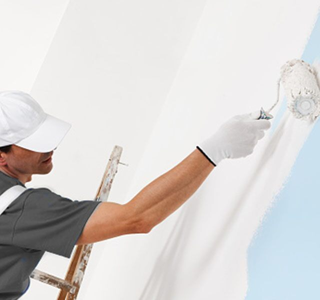 A professional painter uses a paint roller to apply white paint on a wall.