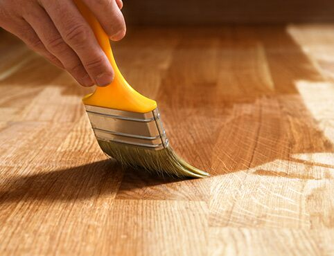 A pro painter refinishes a hardwood floor.
