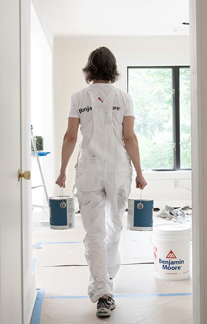 Licensed painter carrying two cans of paint walking down a hall in white overalls