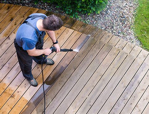 Contractor power washing a deck in preparation for restaining