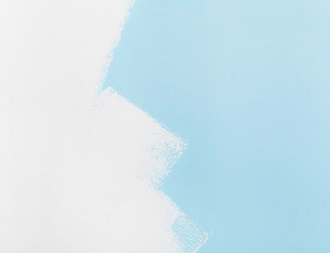A blue wall in the process of being painted white.