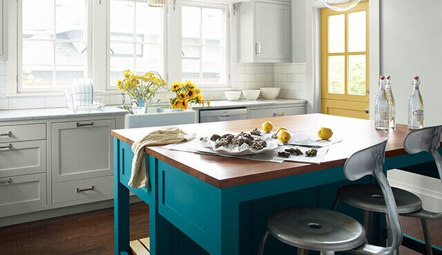 Bright, sun-drenched kitchen with painted yellow door and teal island
