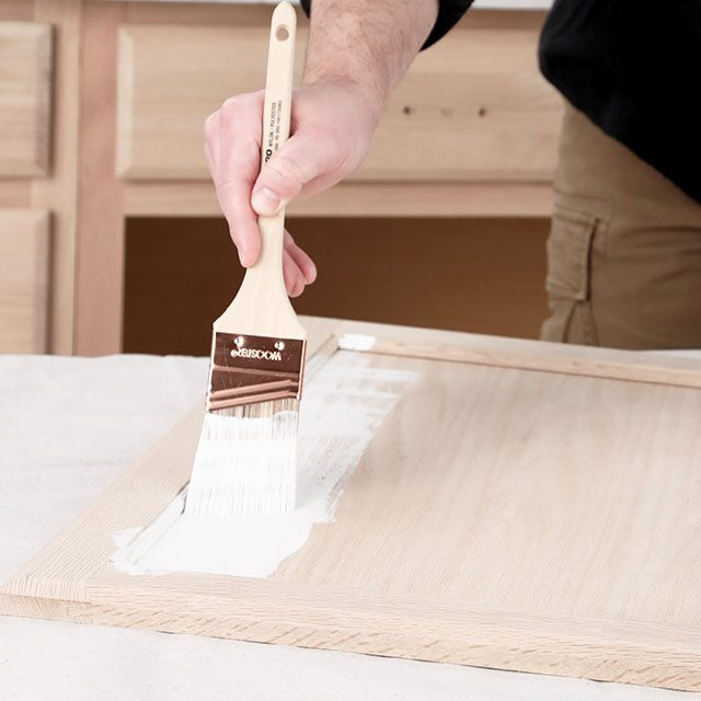 A contractor applying a bonding primer to a cabinet door with a brush