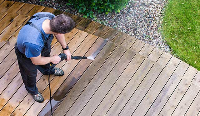 A painting contractor power washing a deck