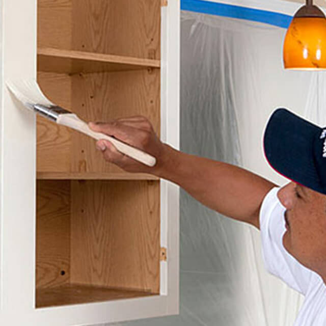 A painting contractor paints a kitchen cabinet