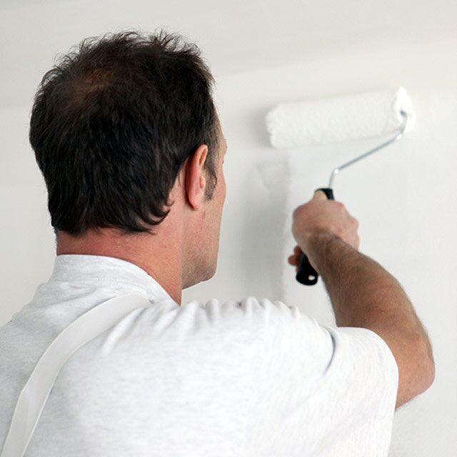 A painting contractor rolls Notable Dry Erase paint on a wall.