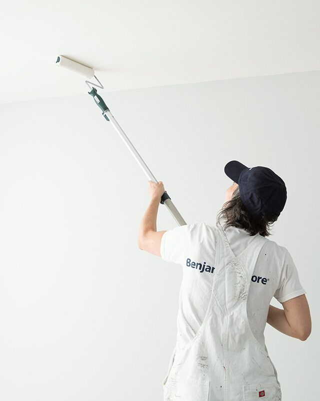 A pro painter rolls paint on a customer's ceiling