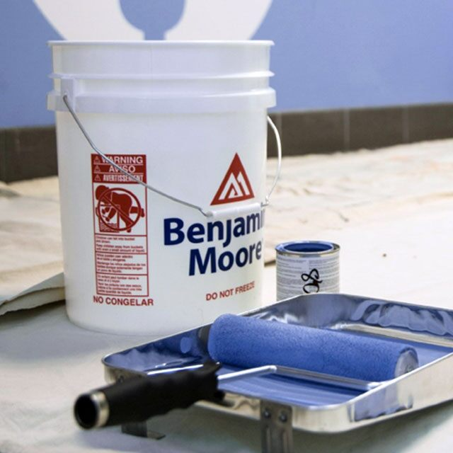Benjamin Moore 5-gallon paint bucket sitting next to a roller cover and tray