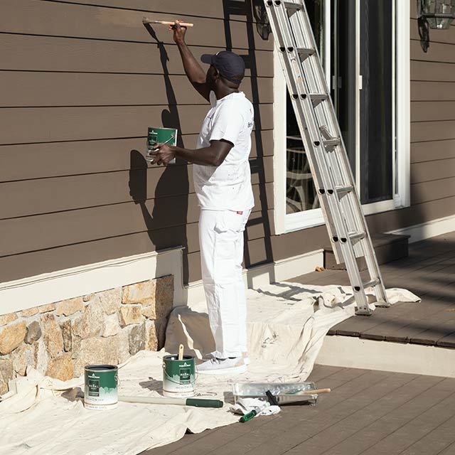 A contractor using a canvas drop cloth on an exterior paint job