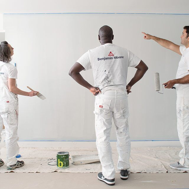 Three painting contractors look at a painted wall