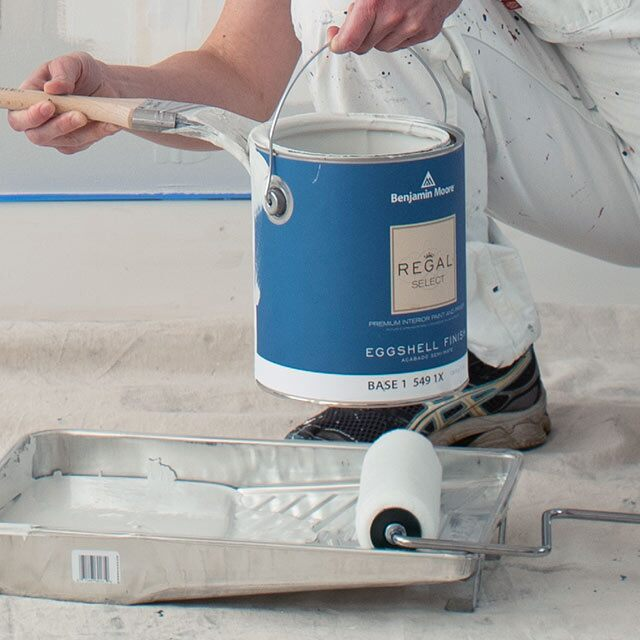 A contractor loads a roller tray with Benjamin Moore® paint