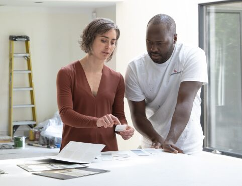 Woman homeowner with a Benjamin Moore contractor discussing her interior paint colour selection