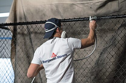 A Benjamin Moore painting contractor spray painting a metal fence using Corotech® COMMAND.