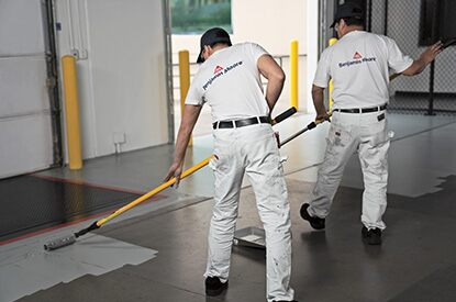 Painting contractors applying Corotech® COMMAND on a warehouse floor.