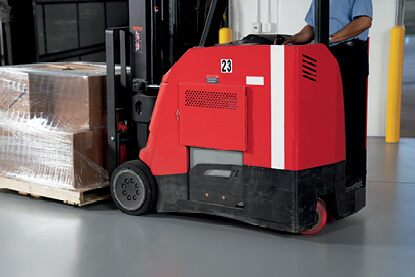 A warehouse employee operating a motorized pallet jack on a floor coated in Corotech® COMMAND.