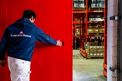 A Benjamin Moore painting contractor opening a large warehouse door painted in Corotech® COMMAND Safety Red.