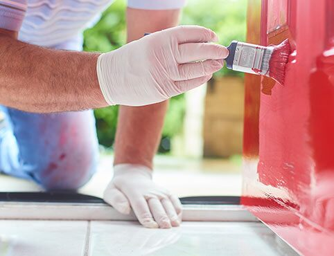 A Benjamin Moore painting contractor paints a red front door.