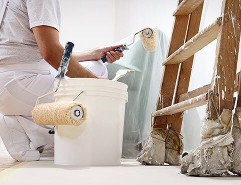 A Benjamin Moore contractor paints a white wall.