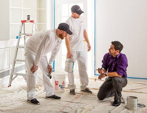 A group of contractors get advice from a Benjamin Moore sales rep.
