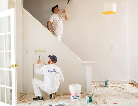 Painting Contractors Work Together in a Home Using Benjamin Moore Paints.
