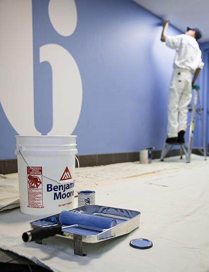 A painting contractor applies blue Benjamin Moore paint tinted with Gennex® Color Technology to a wall.