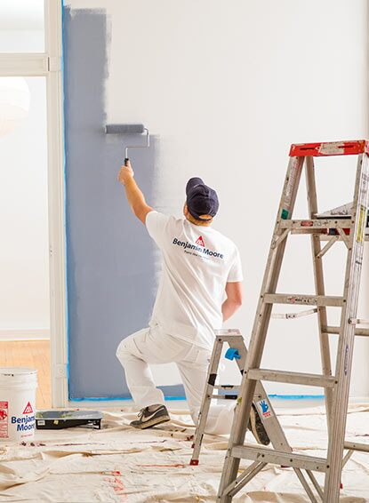 A painting contractor enjoys the ideal application properties of Gennex®-engineered paint while painting a wall.