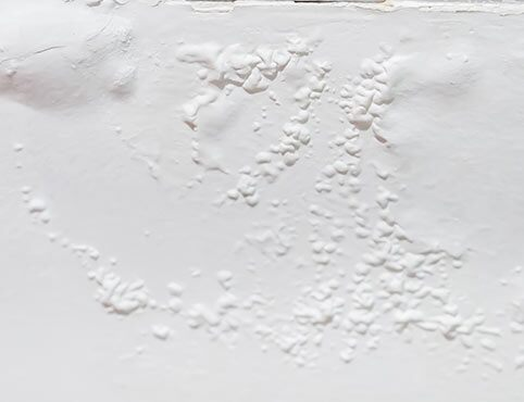 Paint bubbles and blistering appear on a white wall.