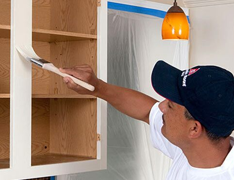 A Benjamin Moore painting contractor paints a wooden cabinet white.