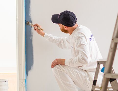 A Benjamin Moore painting contractor paints a wall.