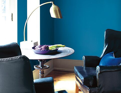Bold blue wall accompanied by leather chairs and a circular table