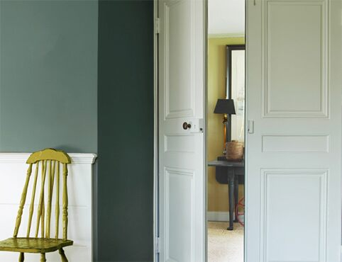 A hallway with white painted doors and a green chair