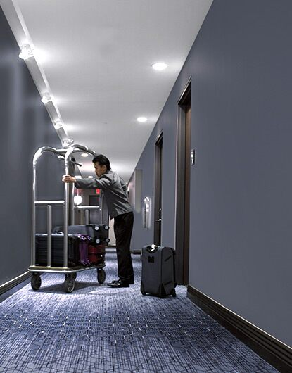 A bellhop unpacks bags from a luggage cart in a hotel hallway where scuffing can be an unsightly problem.