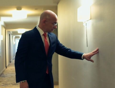 Hotel Expert Anthony Melchiorri inspects a hotel wall for scuffs.