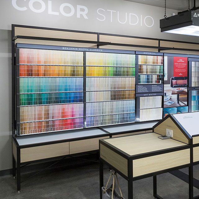 The interior of a Benjamin Moore store features a colour display and products on shelving.