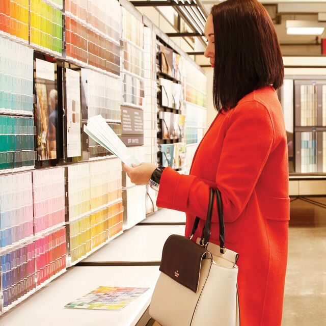 Several customers explore colour options in a Benjamin Moore store.